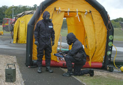 Emergency response personnel using ECAM (chemical agent monitor) at decontamination station.